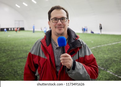 Smiling man with microphone reports from stadium.