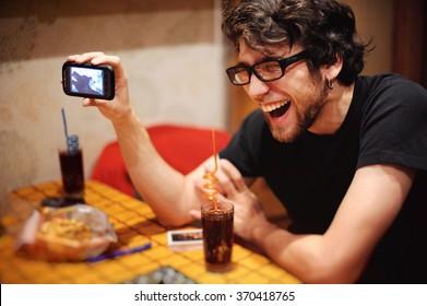 Ein lächelnder Mann mit Handy zeigt einen lustigen Film