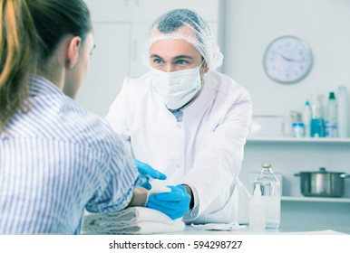 Smiling man nurse making injection to woman patient in hospital