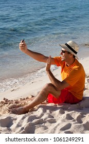 smiling man on the beach taking photos of himself