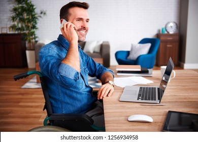 Smiling man on wheelchair talking by mobile phone in home office