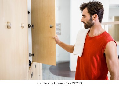 Smiling man opening locker in the gym