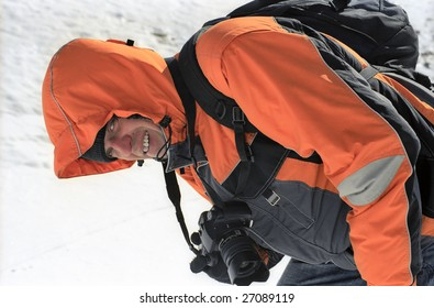 Smiling man in orange sports jacket with photo camera on snow.