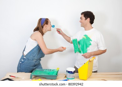 Smiling man painting his wife's nose with paint