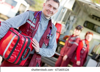 Smiling man paramedic with coworker colleague team emergency medical technicians and rescue bag on ambulance machine background
