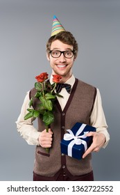 smiling man in party cap holding bouquet of roses and gift box isolated on grey