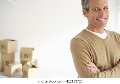 Smiling man portrait on white background and with defocused boxes behind him