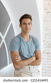 Smiling man. Portrait of young handsome man with crossed hands in casual clothes near window at office.