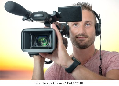 smiling man with professional camcorder and headphones