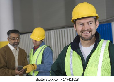 Smiling man in protective wear with colleague in background at factory
