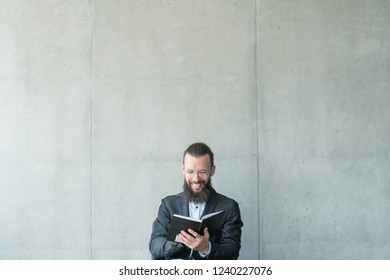 smiling man reading his day planner. information knowledge learning.