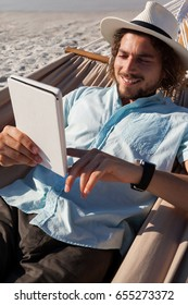 Smiling man relaxing on hammock and using digital tablet on the beach