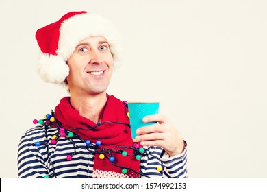 Smiling man in Santa Claus hat holding a paper cup of coffee. Christmas holidays. Christmas sales and discounts. Winter concept. Coffee break for Santa helper. Copy space for text