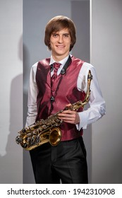 Smiling man with a saxophone in a red vest.