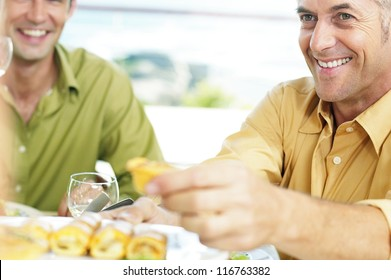 Smiling man seated at a table with friends helps himself to appetizers from a central dish