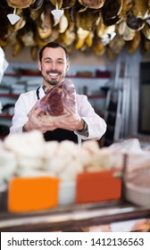 Smiling man seller showing piece of meat in butcher's shop