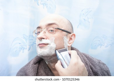Smiling man shaving his beard with electric razor