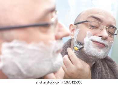 Smiling man shaving his beard at mirror in bathroom