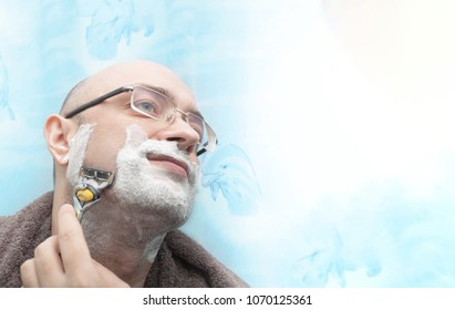 Smiling man shaving his beard by razor blade isolated