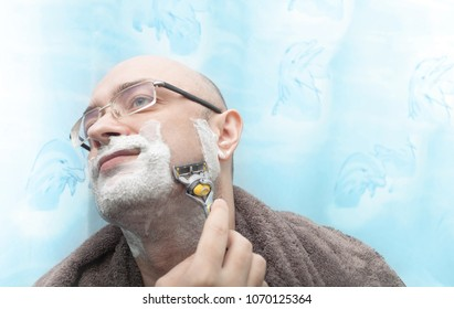 Smiling man shaving his beard by razor blade and look side