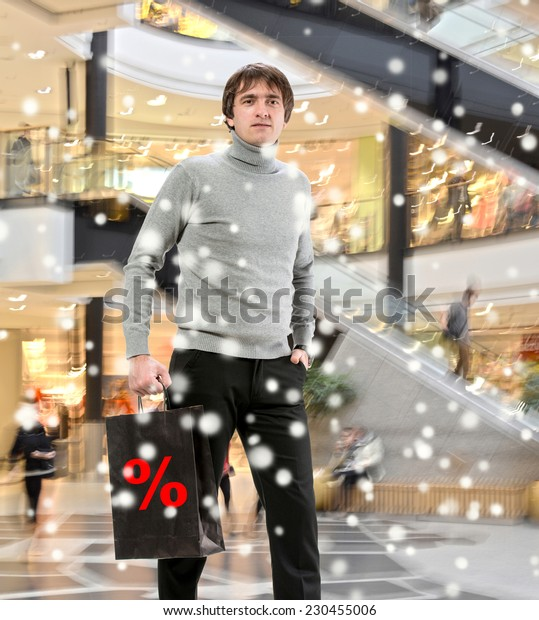 Smiling man  with shopping bag at shopping mall. Christmas and holidays concept