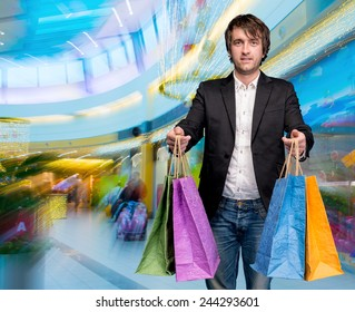 Smiling man with shopping bags in the shopping mall