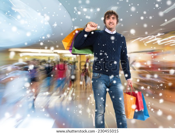 Smiling man with shopping bags at shopping mall. Christmas and holidays concept