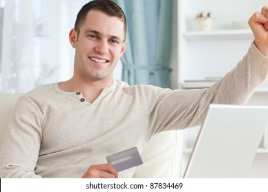 Smiling man shopping online with the fist up in living room