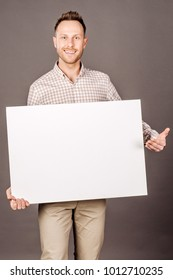 Smiling man show big blank board on grey background. lifestyle and people concept.