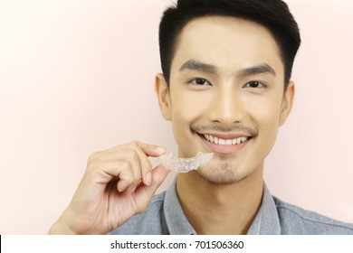 Smiling man with silicone trainer close up for more whitening teeth, hand holding Invisible braces for home whitening or bleaching gel tray opalescence.