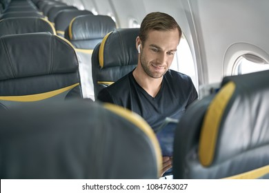 Smiling man sits in the airplane next to the window on the background of the empty seats. He wears a black T-shirt and wireless headphones and reads a magazine. Closeup. Horizontal.