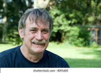 smiling man, sitting in his backyard