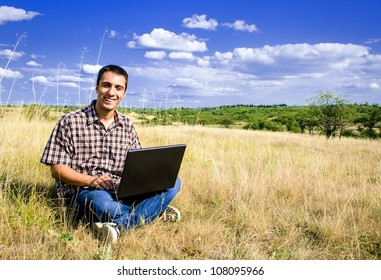 Smiling man sitting in nature with laptop in his lap