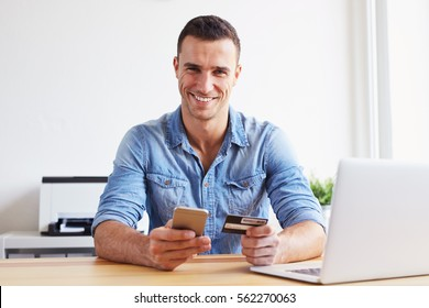 Smiling man sitting in office and pays by credit card with his mobile phone