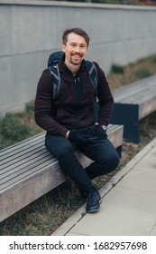 smiling man sitting on the bench. The young man has a backpack on his back. Weather jes slightly cloudy - Shutterstock ID 1682957698