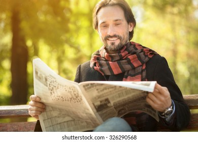 Smiling man sitting on the bench and looking into newpaper. Man sitting on the bench in the park and reading about latest events.
