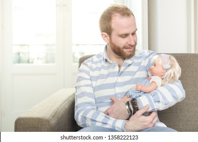 Smiling Man Sitting on a Couch Cradling a Doll