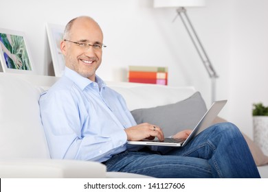 Smiling man sitting on the couch and browsing the internet
