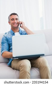 Smiling man sitting on couch phoning and using laptop at home in the living room