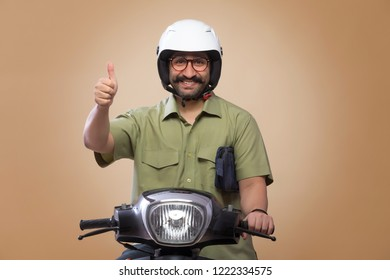 Smiling man with a small bag in his arms riding scooter wearing a helmet and showing thumbs up sign.