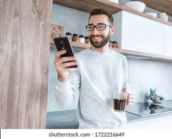 smiling man with smartphone and Cup of coffee standing in his kitchen