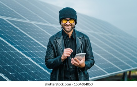 Smiling man stand beside of solar panels with tablet in hand