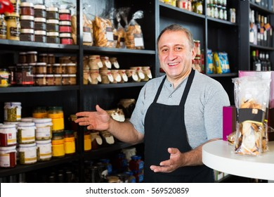 smiling  man standing near counter with assortment of grocery products