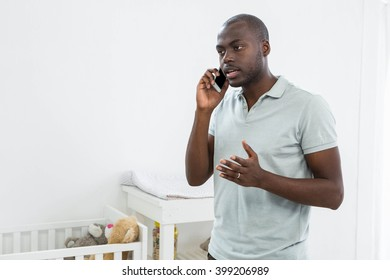 Smiling man standing next to a cradle and talking on mobile phone at home