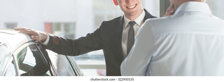 Smiling man in suit holding hand on his new modern car