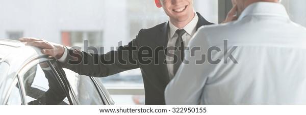Lächelnder Mann in Anzug, der Hand an seinem neuen modernen Auto hält