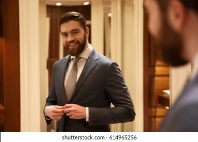 Smiling man in suit looking at the mirror while being in the shop