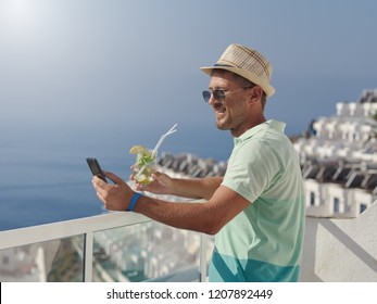 Smiling man in sunhat relaxing on resort balcony 3588ccee04cf