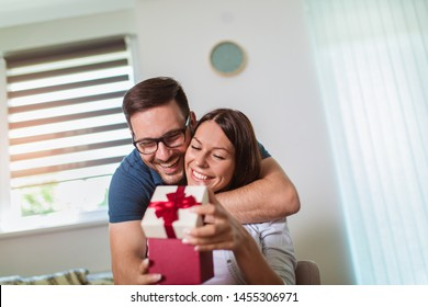 Smiling man surprises his girlfriend with present at home