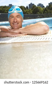 smiling man in a swimming wearing swimming cap and goggles on his head, his arms resting at the edge of swimming pool